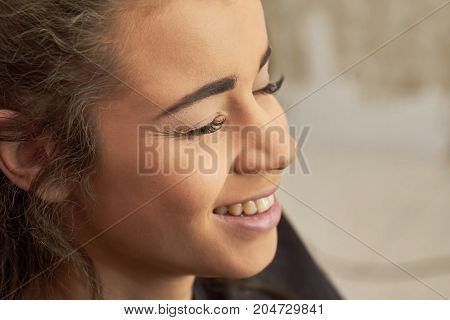 Face of young woman smiling. Pretty girl with closed eyes. Beautiful and happy.