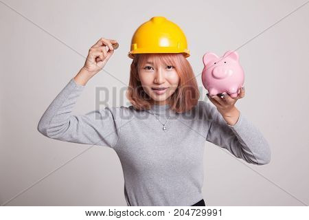 Asian Engineer Woman With A Coin And Piggy Coin Bank.