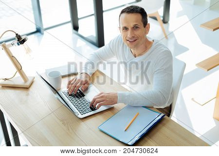 Successful manager. Attractive happy smart man looking at you and being in a good mood while working on the laptop