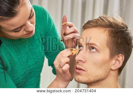Visagist applying foundation, male model. Work of makeup artist. Best foundation for dry skin.