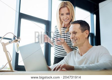 What is this. Delighted positive blonde woman holding a cup with tea and pointing at the laptop screen while standing near her male colleague