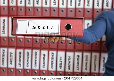 Skill Business Concept. Skill Concept. Young Man Holding Ring Binder.