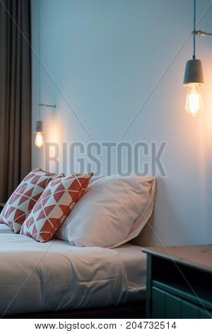 Trendy Hotel Room With Retro Lightbulbs Hanging On Wall Above Bed.