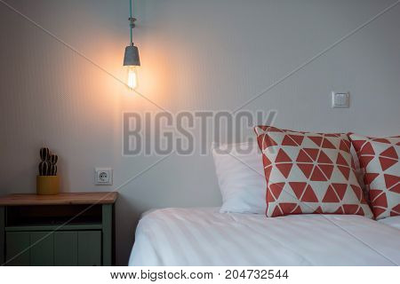 Hotel Bedroom With Vintage Lightbulb Hanging On Wall.