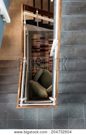 Top View Of Industrial Stairwell With Armchair On The Ground Floor.
