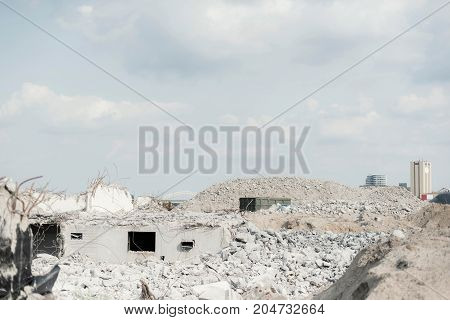 Construction Site With Demolished Buildings And Building Materials Under Cloudy Sky.