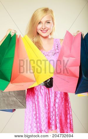 Buying things shopaholic spending money on clothes concept. Happy woman in short pink dress with shopping bags. Studio shot on light background