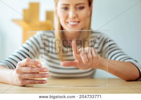 Innovative tablet. Selective focus of a modern electronic device being in hands of a cheerful smart positive woman