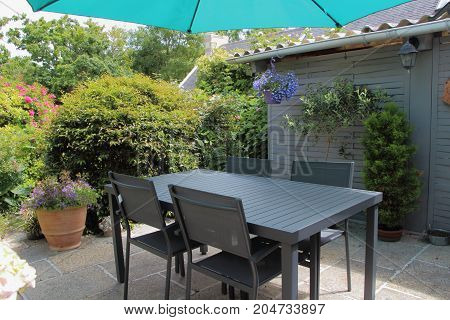 Flowered terrace with flowerpots gray garden furniture and green sunshade during spring
