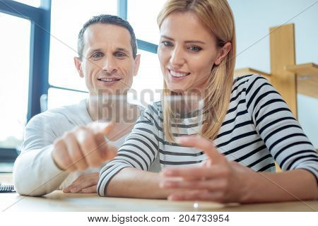 Professional collaboration. Cheerful nice handsome man sitting together with his colleague and pointing at the tablet screen while working