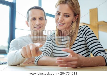 What is this. Delighted nice pleasant man smiling and pointing at the tablet screen while sitting together with his colleague