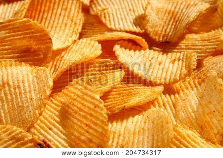 Background Of Crispy Golden Chips With Ribbed Texture, Seasoned, With Sunlight. Frame For Wallpapers