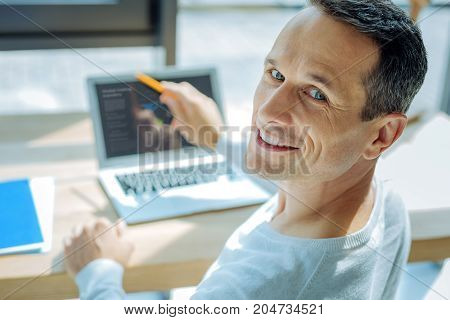 Statistical data. Pleasant good looking handsome man smiling and pointing at the laptop screen while turning to you