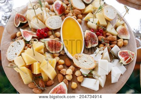 Assortment of cheese on wooden board. a buffet table at a party outdoors