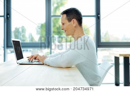 Global market. Pleasant smart ambitious businessman looking at the laptop screen and studying global market while working