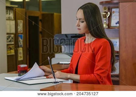 Secretary In A Red Suit Puts A Stamp In The Incoming Messages. Office Work, Document Control