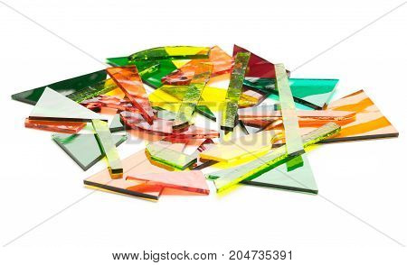 Broken pieces of coloured stained glass on a white background