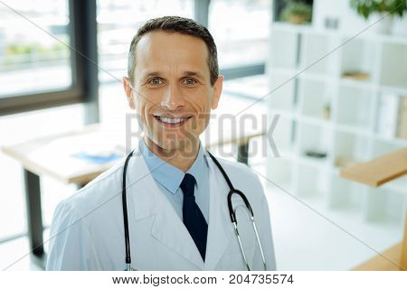 At the hospital. Portrait of a professional skillful handsome doctor wearing a labcoat and smiling while being at work