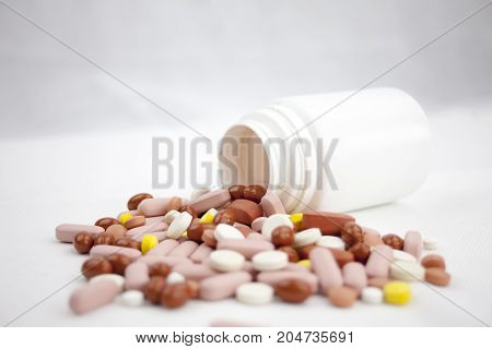 Colorful Pills Laying On The White Background With Empty Bottles
