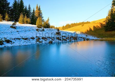 The fantastic view of the mountains and lawns covered with snow is opened from the coast. The lake with frozen water interesting frost and texture.