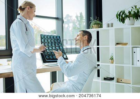 What do you think. Cheerful smart experienced neurologist holding an X ray scan and talking to his colleague while asking her opinion about it