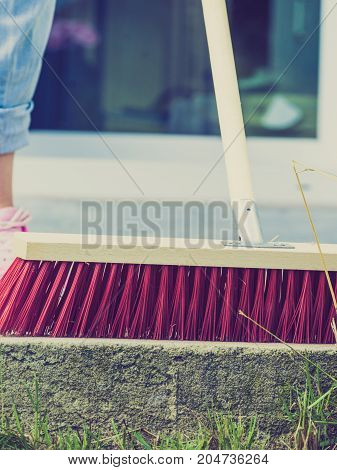 Unrecognizable female person using big broom to clean up backyard patio