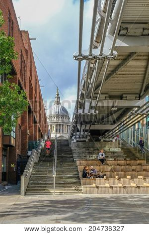 London Uk - August 3 2017: View of St. Paul's Cathedral from the riverside underneath the Millennium Bridge. Daytime shot with jogger running down the stairs.