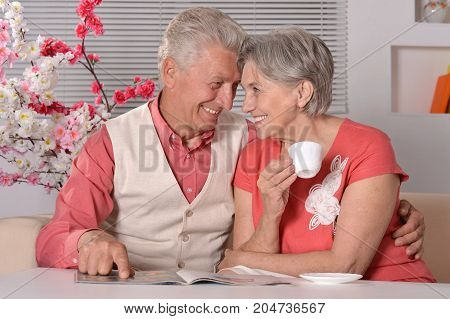 Happy senior couple drinking tea  and reading magazine