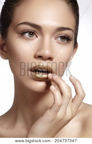 Young Beautiful Woman with clean soft Skin bright gold Lips Makeup. Perfect eyebrows shapes. Day look make-up with gloss