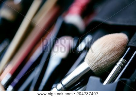 Set of make-up brushes in black makeup bag. Beauty tools for professional visage. Brushes for maskara eyeshadows foundation lipstick blush and facial cream