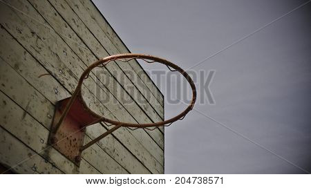 Old red basketball basket on the background in sky. Monochrome photography.