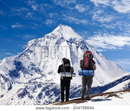 View of mount Dhaulagiri with two tourists great himalayan trail Nepal