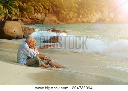 Happy elderly couple resting  at tropical beach pointing with finger