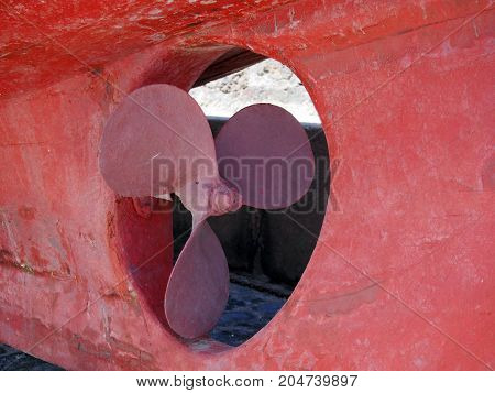 propellor on an old red wooden fishing boat