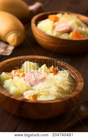 Sauerkraut soup or stew prepared with potato carrot and bratwurst served in wooden bowls photographed with natural light (Selective Focus Focus in the middle of the first dish)