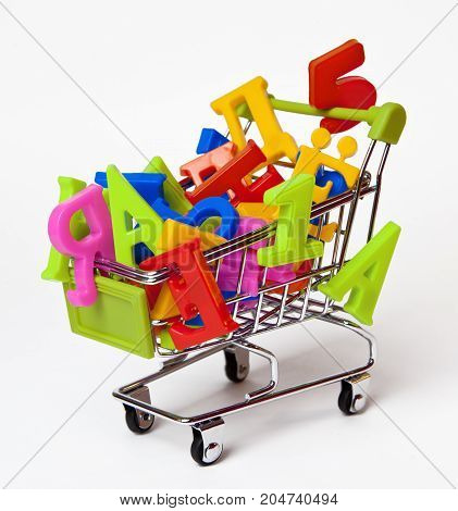 Russian multi-colored magnetic letters and numbers in the small grocery cart on a white background.