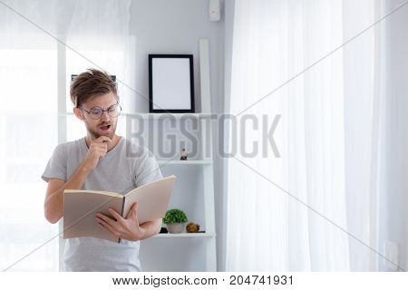 Handsome guy in eyeglasses is reading book preparing exam and thinking with standing at the living room - education concept.