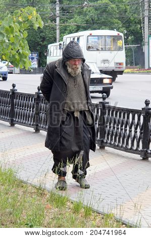 Voronezh, Russia - Circa 2014: Homeless sad old man walking along street