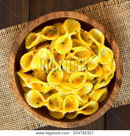 Pasta with pumpkin and parsley sauce served in wooden bowl photographed overhead on dark wood with natural light (Selective Focus Focus on the top of the dish)