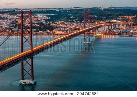 Sunset over the ' 25 April ' bridge with reflection of the lights of the cars in the road, in Lisbon, capital of Portugal