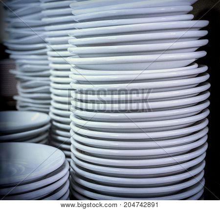 Several white dishes piled up, conceptual image