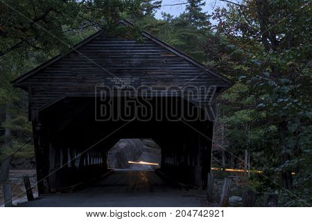 Albany New Hampshire USA - September 29 2010: Headlights of approaching car reflecting off deck of Albany Covered Bridge ar dusk