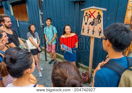 KYOTO, JAPAN - JULY 05, 2017: Crowd of people listening at tourist girl the advice and recomendations to visit in the city on Gion district in Ky, Japan.
