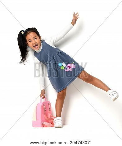 Happy young little child girl with backpack for first class expressing positivity on white background