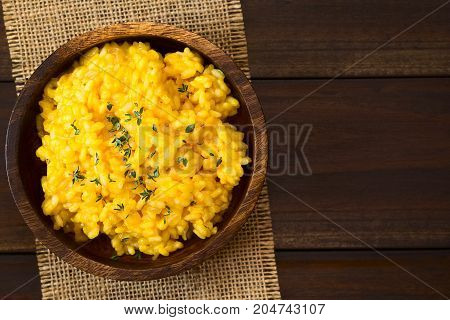 Pumpkin risotto prepared with pumpkin puree and sprinkled with fresh thyme leaves served in wooden bowl photographed overhead on dark wood with natural light (Selective Focus Focus on the top of the risotto)