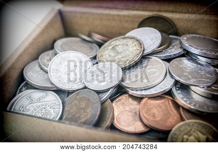 Some ancient coins in a cardboard box
