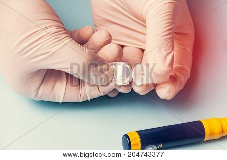 A Man In Medical Gloves Holds A Small Thin Needle For Subcutaneous Injection Of Hormonal Drugs In Th