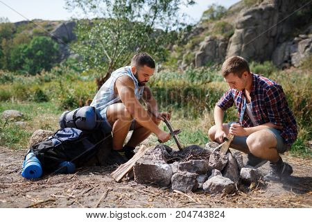 Two young male tourists in the wood, organizing the camp fire for barbeque, helping each other, team work, sunny day, green forest, girls are unpacking, gossipping. Beautiful sunny day, leisure time.