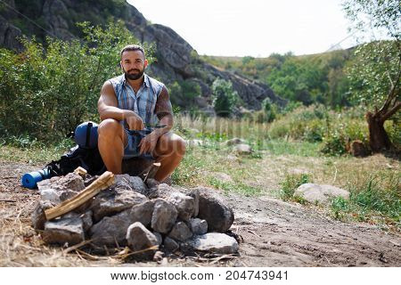 Young man traveler hiking and watching the scenic landscape view. Travel lifestyle concept photo with beautiful mountain and evergreen trees on background. Summer vacations activity outdoor