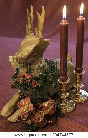 vertical Christmas table decoration with paper mache deer and red candles in brass holders